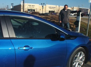 "David Nichols of Yates City stands next to his 2016 Chevy Volt, one of three electric cars he's owned or leased since 2011. Nichols commutes 53 miles daily to work in Peoria and frequently uses the public charging stations in the area to ""top off"" his car's charge."