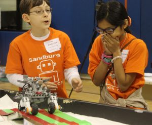 Sandburg Middle School (Elmhurst) students Bradley Dow and Stephanie Longoria cheer their DogBot through obstacles during a table run. The 2016 DogBot challenge required each 4-H team to design a robot and program it to perform agility and obedience tasks similar to that of a trained dog, such as running obstacles.  (Photo courtesy University of Illinois Extension)
