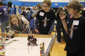 """Team #Awesome of Kendall County earned Top Dog honors for this year's DogBot Challenge at the 4-H Robotics Showcase in Elgin. 4-H'ers William Davis of Newark and Adam Hartford of Yorkville watch one of their """"DogBots"""" run the poles obstacle, as a judge evaluates the performance. (Photo courtesy University of Illinois Extension)"""