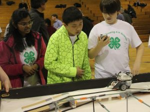 """Members of Team """"We Forget"""" watch and time one of their table runs during the 4-H Robotics Showcase on April 9 in Elgin. The group from Herrick Middle School in Downers Grove won an award for Best Table Performance with One Robot. (Photo courtesy University of Illinois Extension)"""