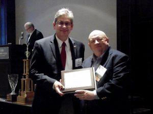 Chronicle Media Editor-in-Chief Rick Hibbert (left) accepts an award on behalf of writer Paul Sassone for Best Original Column from Illinois Press Association Board Member Gary Sawyer. Photo / Illinois Press Association