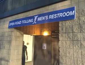 Restrooms were adorned with I-Pass-like signs at the Kane County Cougars corruption-themed game. (INN Photo by Cole Lauterbach)