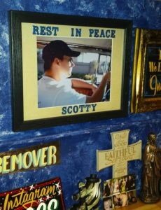 Chris Baker's work station at his Oswego tattoo shop INK180 sits a picture of his friend Scott who committed suicide several years ago. The picture, as well as Baker's semicolon tattoo, help keep his friend's memory alive, he said. (Photo by By Erika Wurst for Chronicle Media)