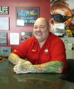 Oswego tattoo artist Chris Baker poses for a portrait at his shop, INK180, which is holding a promotion on semicolon tattoos throughout the month of August. The tattoos are Baker's attempt at raising awareness of suicide, mental illness and addiction.(Photo by By Erika Wurst for Chronicle Media)