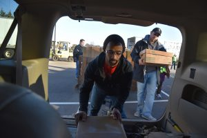 Pastor Charles Amoh (left), assisting Rogers Park-based Family Empowerment Center, loads frozen chicken into a van on Nov. 12, 2016 at the UL headquarters in Northbrook for Community Outreach Day by Hunger Resource Network of Northbrook. On right is John Martinez of Family Empowerment Center of Rogers Park.(By Karie Angell Luc/for Chronicle Media)