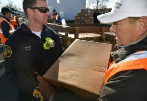 Lieutenant Steve Morris (left) of the Northbrook Fire Department passes frozen chicken boxes to John Golab of Barrington on Nov. 12, 2016 at the UL headquarters in Northbrook for Community Outreach Day by Hunger Resource Network of Northbrook.(By Karie Angell Luc/for Chronicle Media)