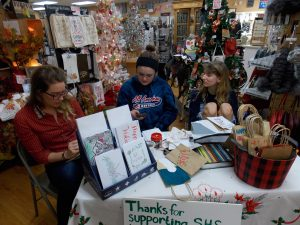 Sycamore High School students took advantage of last week's Small Business Saturday to offer custom-made holiday cards and gift bags at a table set up inside Sweet Earth on State St. (Photo by Jack McCarthy / Chronicle Media)