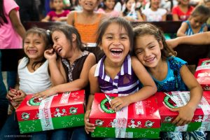 Young girls react with joy after receiving their Operation Christmas shoe boxes. First Baptist Church of Sycamore is collecting donations for the effort that over the years has gift-filled shoe boxes to more than 135 million children in 150 countries.