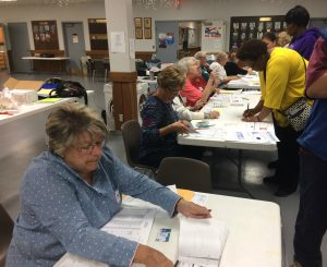 Volunteers at Tazewell County'sU.A.W. Local #974 Hallin East Peoria assist early morning votersto verify voter registration and hand out ballots on Nov. 8. (Photo by Holly Eitenmiller / for Chronicle Media)